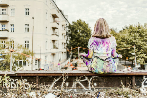 Girl with Holi colours on her clothes sitting on bridge, Germany - VGPF00043