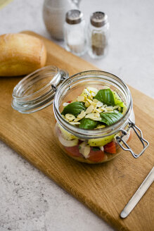 Glass of salad with cucumbers, chickpeas, onion, cherry tomatoes, basil, chia seed and sliced almonds - GIOF06366