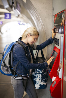 Smiling woman using ticket machine at the station - HMEF00402