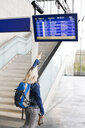 Woman checking the departures board at the station - HMEF00408