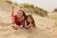 Portrait of two smiling girls lying on the beach - NMS00310