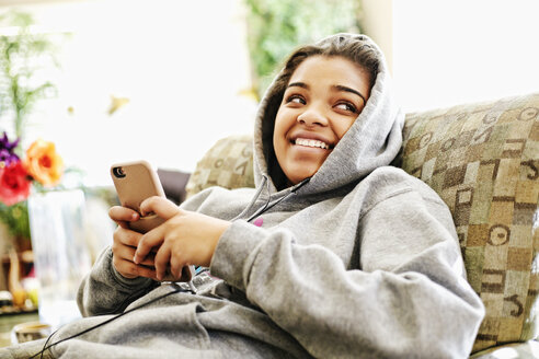 Mixed Race woman sitting on chair listening to cell phone - BLEF04600