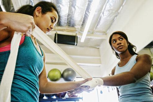 Woman wrapping hands of friend in gymnasium - BLEF04603