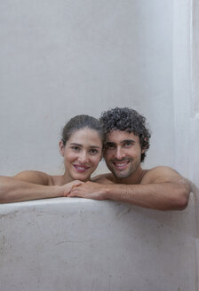 Smiling Caucasian couple relaxing in bathtub - BLEF04678