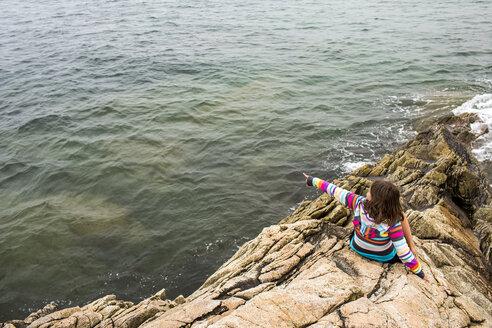 Caucasian girl sitting on rocks pointing at ocean - BLEF04693