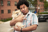 Mixed Race man gesturing peace with dog in city - BLEF04792