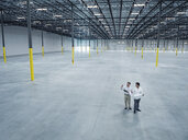 Architects with blueprint talking in empty warehouse - BLEF04840