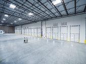 Businessmen walking near loading docks in empty warehouse - BLEF04843