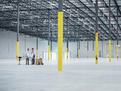 Architects using blueprint in empty warehouse - BLEF04849