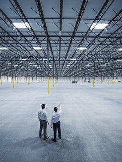 Businessmen talking in empty warehouse - BLEF04885