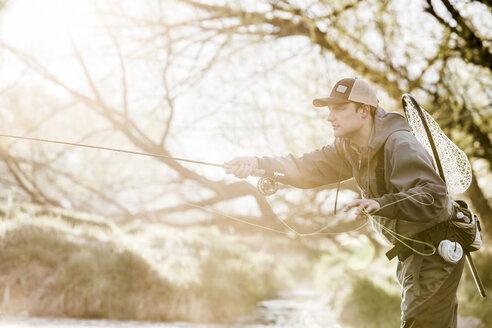 Caucasian man fly fishing in river - BLEF04972