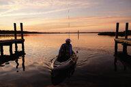 Caucasian man on kayak near dock at sunset - BLEF05107