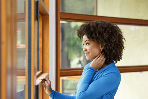 Smiling Black woman looking out window - BLEF05113
