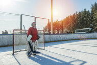 Caucasian boy playing goalie in ice hockey outdoors - BLEF05119