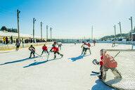 Caucasian boys playing ice hockey outdoors - BLEF05125