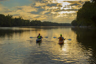 Couple kayaking in river at sunset - BLEF05269