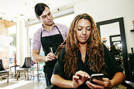 Hairdresser with customer texting on cell phone in hair salon - BLEF05389