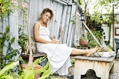 Smiling Mixed Race woman drinking coffee in garden - BLEF05404