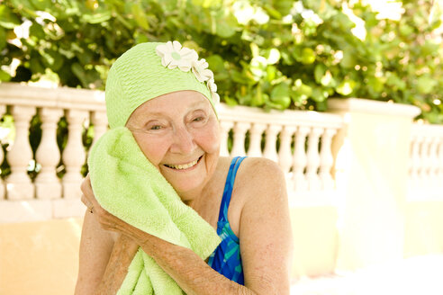 Older Caucasian woman drying with towel after swimming - BLEF05434