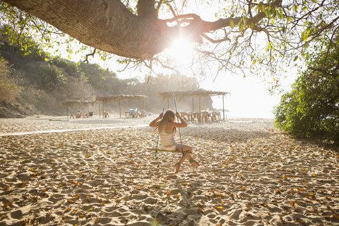 Caucasian girl sitting on tree swing - BLEF05512