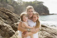 Caucasian mother hugging son and daughter at beach - BLEF05521