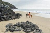 Caucasian mother and children walking on beach - BLEF05530