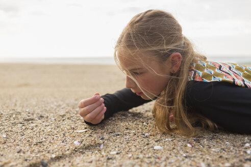 Caucasian girl laying on beach examining seashells - BLEF05533