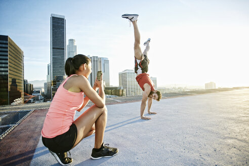 Woman photographing man doing handstand on urban rooftop - BLEF05551
