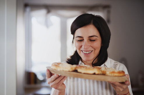 Mature woman serving homemade cakes ona wooden tray - HAPF02910