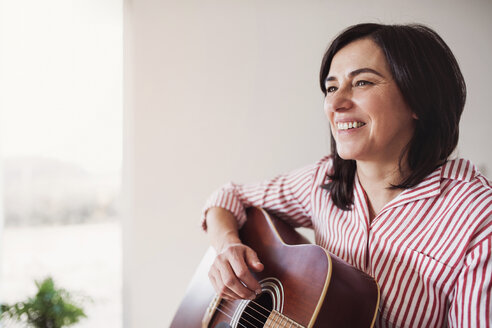 Portrait of smiling mature woman playing guitar at home - HAPF02958