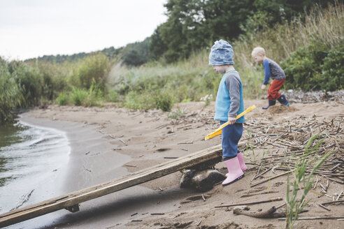 Boy and girl playing on a wild sand beach - IHF00044
