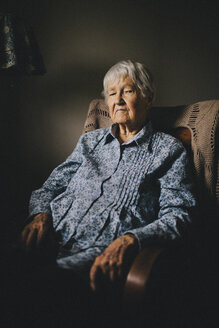 Older mixed race woman sitting in armchair - BLEF05631