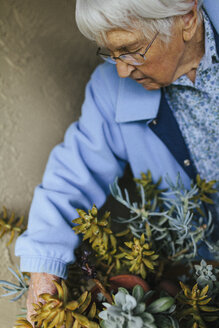 Older mixed race woman caring for potted plants - BLEF05637