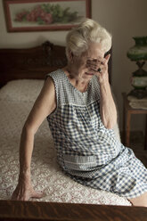 Sad older woman crying on bed - BLEF05655