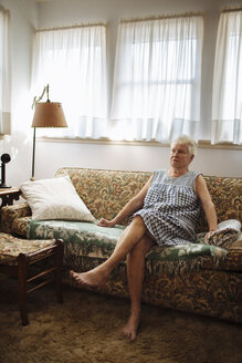 Older woman sitting on sofa in living room - BLEF05661