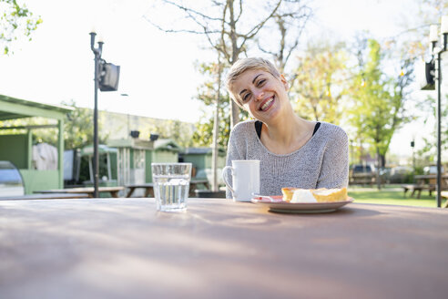 Portrait of smiling woman with cup of coffee and piece of cake outdoors - FBAF00606