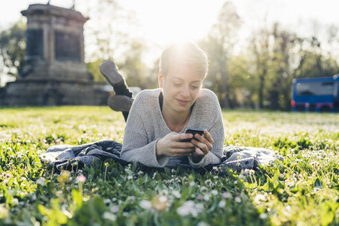 Smiling young woman lying on a meadow at backlight looking at cell phone - FBAF00612