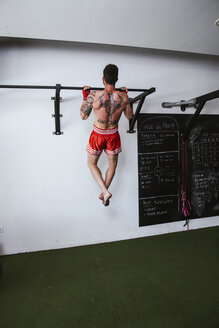 Kickboxer training in fitness studio, chin-up - LJF00025
