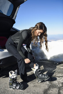 Woman siiting in boot of a car putting on ski boots - JSMF01092