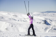 Happy woman raising her ski poles in snow-covered landscape in Sierra Nevada, Andalusia, Spain - JSMF01101