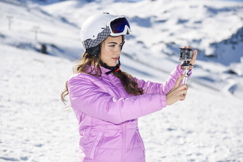 Woman in ski clothes filming with an action camera in snow covered-landscape - JSMF01110