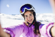 Selfie of young woman in ski clothes in snow covered-landscape - JSMF01113