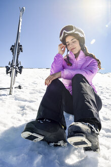 Woman taking a break after skiing sitting on the snowy ground in Sierra Nevada, Andalusia, Spain - JSMF01131