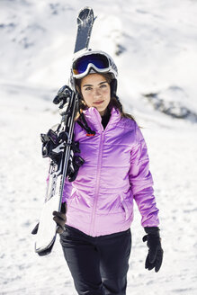 Portrait of woman carrying her skis over her shoulder, Sierra Nevada, Andalusia, Spain - JSMF01134