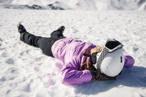 Woman taking a break after skiing lying on the snowy ground in Sierra Nevada, Andalusia, Spain - JSMF01137