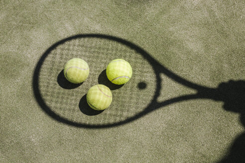 Shadow of a tennis player with balls and racket on court - LJF00041