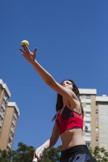 Female tennis player playing on court in the city - LJF00062