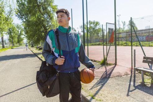 Young man with basketball at basketball court - MGIF00480