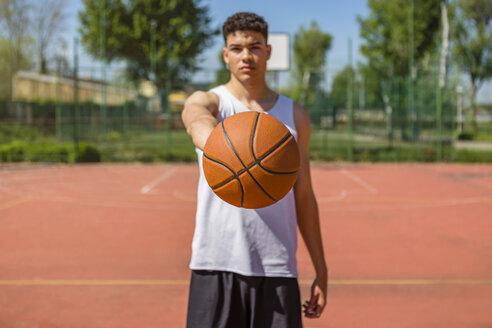 Young man playing basketball, giving the basketball - MGIF00498