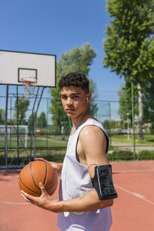 Young man playing basketball, smartphone in arm pocket - MGIF00516